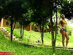 Feminine shemale in yellow bikini showcases her round boobs