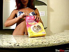 Redhead tranny in colorful bikini masturbates in the kitchen