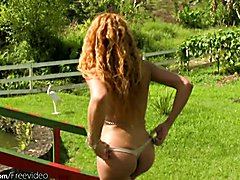 Curly hair t-girl poses outdoors and shows huge ass in thong
