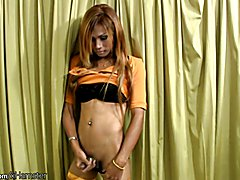Petite ladyboy in orange stockings shows her puffy asshole