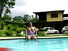 Tranny in pink corset fools around the pool and jerks off